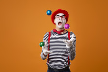 Mime In Vest And Red Hat Juggl...
