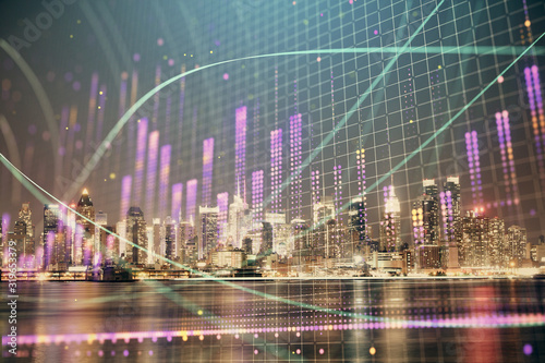 Fototapeta Financial graph on night city scape with tall buildings background multi exposure. Analysis concept. obraz