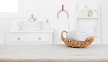 Towel In Basket On Wooden Table Over Blurred Bathroom Background