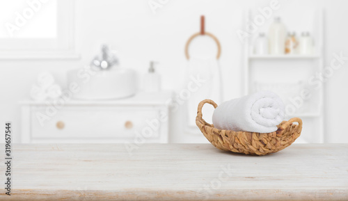Fototapeta Towel in basket on wooden table over blurred bathroom background obraz