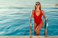 Attractive Woman In Red Swimsuit And Sunglasses Coming Out Of The Pool