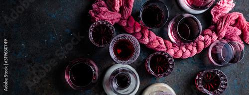 Fototapeta Glasses of red wine and corkscrews on grey background obraz