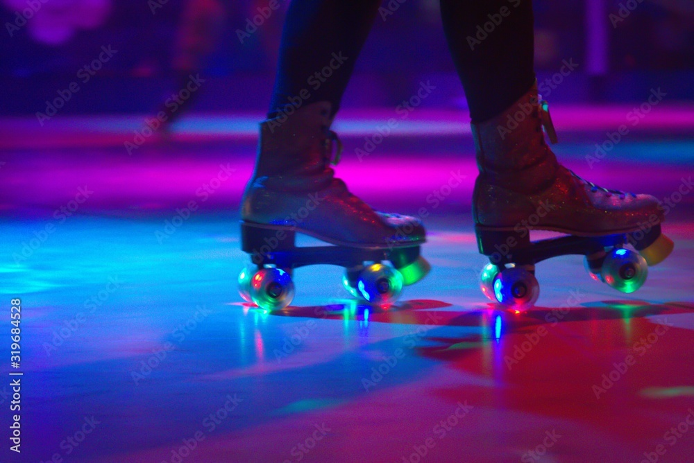 Fototapeta Low Section Of Person Roller Skating On Floor In Illuminated Rink