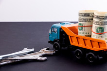 Truck With A Load Of Money And Wrenches On A Black Background
