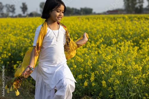 Fototapeta child and mustard flower