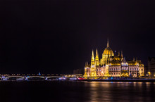 Hungarian Parliament Building By Danube River At Night