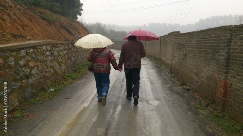 Stampa su Tela REAR VIEW OF COUPLE WALKING ON ROAD