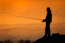 Side View Of Silhouette Teenage Boy Fishing In Sea During Sunset