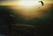 Man Photographing Silhouette Person Paragliding Over Landscape During Sunset