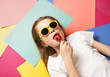 Vibrant colors: a child girl lies on a colorful background and licks a lollipop.
