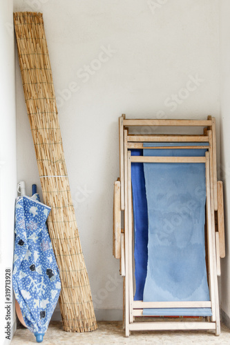 Rolled Beach Mat And Umbrella With Folded Deck Chair Leaning On Wall Fototapet