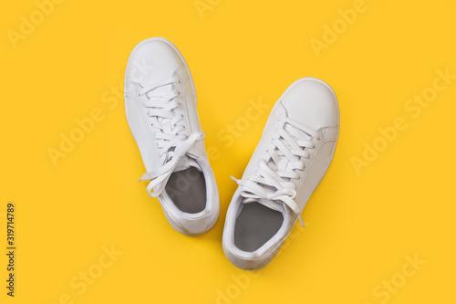 Zapatillas blanca sobre fondo amarillo liso brillante Obraz na płótnie