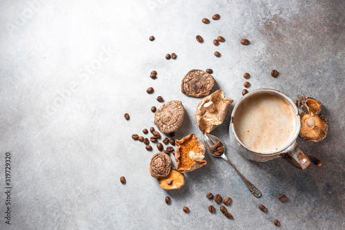 Obraz Mushroom coffee, a ceramic cup, mushrooms and coffee beans on stone concrete background. New Superfood Trend. - fototapety do salonu