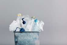 Heap Of Plastic Bottles, Cups, Bags Collected To Recycling In A Metal Bin. Concept Of Plastic Pollution And Too Many Plastic Waste. Trash With Used Plastic Packagings Over Grey Background