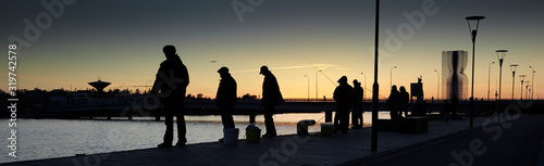 Fishermen on the waterfront catch fish at sunset. Wallpaper Mural