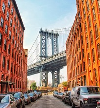 Row Of Cars Parked On Street Amidst Buildings With Manhattan Bridge Seen In Background