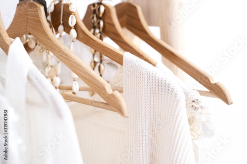 Detail of white clothes hanging on wooden hangers in a fashion store Fototapete