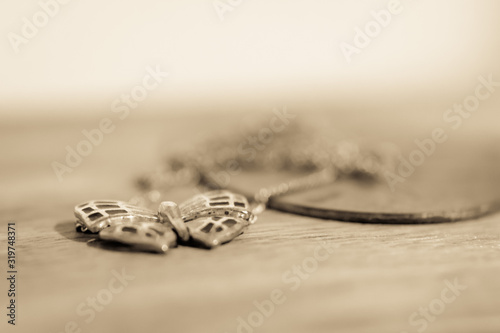 Fotografie, Tablou Close-Up Of Butterfly Shaped Pedant In Necklace On Table