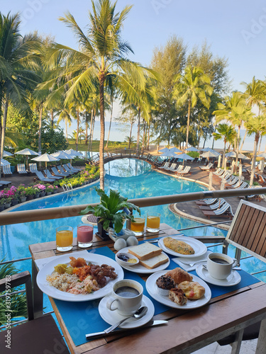 Fototapeta luxury hotel with breakfast table and a look at the swimming pool and ocean in Thailand obraz