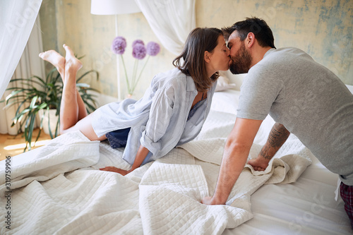 Fototapeta young sexy couple in underwear having a kiss in bed in the morinig on valentines day. Intimacy, passion, erotic concept. obraz