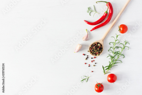 Obraz na płótnie Composition of colorful pepper seeds, fresh chili pepper, tomatoes, garlic and rosemary herb top view on white wooden background