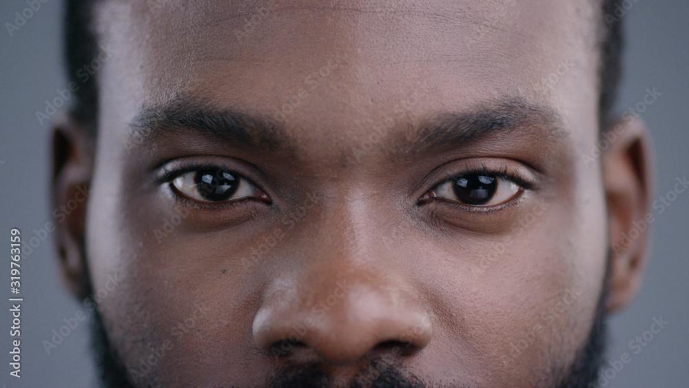 Fototapeta Close-up of beautiful black man eyes staring at camera. Portrait detail of serious confident african american man.