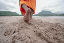 Low Section Of Monk Walking On Sand