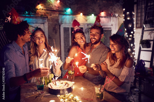 Fotomural Smiling group of young friends having  birthday party in the club with cake and candles at night