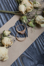 Wedding Rings Lie On Paper With A Cut Out Heart. Nearby Dried Roses. On Brushed Pine Boards Painted In Black And White.