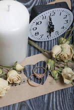 Wedding Rings Lie On Paper With A Cut Out Heart. Nearby Are Dried Roses And A Clock. On Brushed Pine Boards Painted In Black And White.