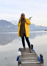Full Length Of Woman Standing On Pier Over Lake Against Snow Covered Mountain
