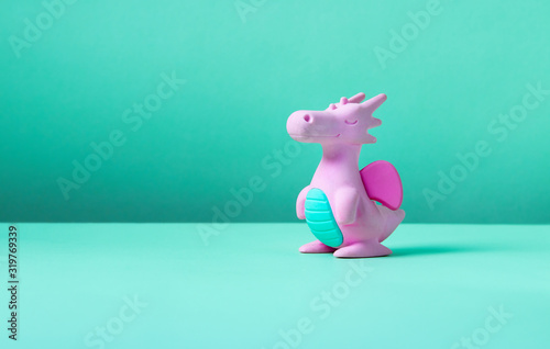 Cute rubber dragon toy on green background. Fotobehang