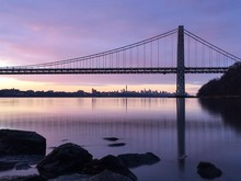 George Washington Bridge Over Hudson River Against Purple Sky During Sunset