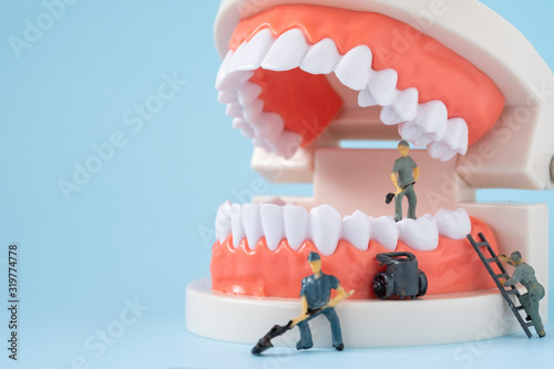 Photo Miniature people of the teeth cleaning workers are medical and health care concepts