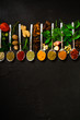 Colourful various herbs and spices for cooking on dark background.