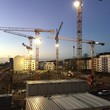 Illuminated Construction Cranes Against Sky