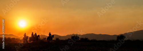 Papel de parede Silhouette cowboy group riding horseback in farm at sunset, landscape panorama,