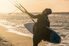 Portrait Of A Wave Kitesurfer Walking Upwind At The Beach With His Board And A Kite In Beautiful Yellow Sunset Conditions