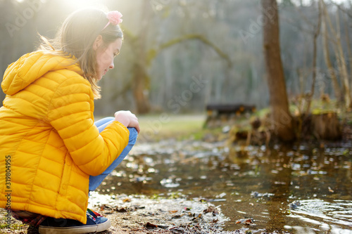 Obraz Cute young girl having fun by a river on warm spring day. Child playing by a water. - fototapety do salonu