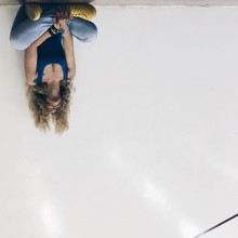 Upside Down Image Of Woman Sitting Against White Wall