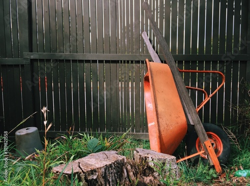 Abandoned Orange Wheelbarrow In Back Yard Against Fence Fotobehang
