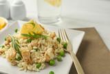 Fototapeta Kawa jest smaczna - Delicious chicken risotto with lemon on table, closeup