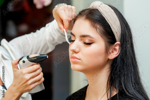 Photo Beautiful young brunette woman receiving airbrush makeup by makeup artist
