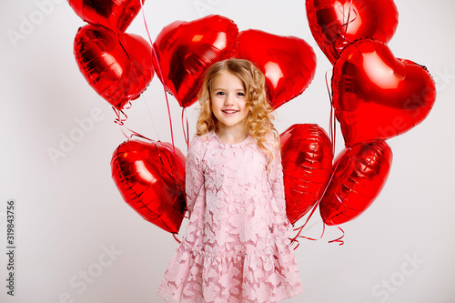 Платно little blonde girl in a pink dress is smiling and holding a lot of red heart-shaped balloons, space for text