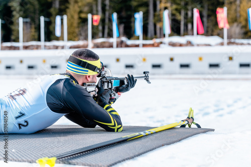 Photo Biathlete shooting with a rifle at a shooting range at the race