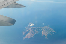 A Small Island On An Open Sea Seen From A Plane's Window While Flying Over Indonesia. In The Corner There Is An Air Plane Wing Visible. Top Down Perspective.