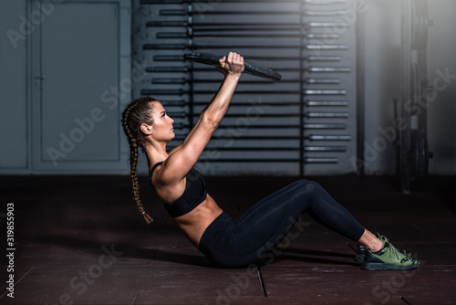 Photo Young strong sweaty fit muscular girl with big muscles doing sit ups with barbel