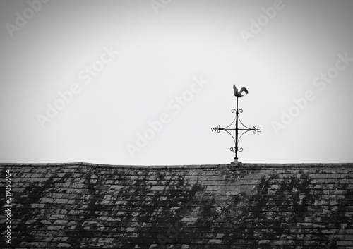 Tableau sur Toile Low Angle View Of Weather Vane On Old House Roof Against Sky