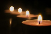 Close-Up Of Lit Candles In Rows