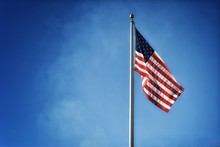 Low Angle View Of American Flag On Pole Against Blue Sky